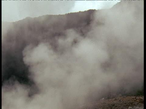 vídeos de stock e filmes b-roll de tilt down steaming volcanic landscape to reveal bubbling yellow vent releasing sulfurous gases, java - evolução