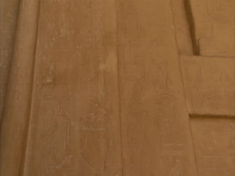 tilt down stone wall engraved with ancient egyptian hieroglyphics, sakkara, egypt (sound available) - saqqara stock videos and b-roll footage