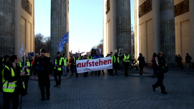 """tilt down, supporters of the new left-wing """"stand up"""" movement gather at a demonstration which started at potsdamer platz and ended here at the... - links platz stock-videos und b-roll-filmmaterial"""