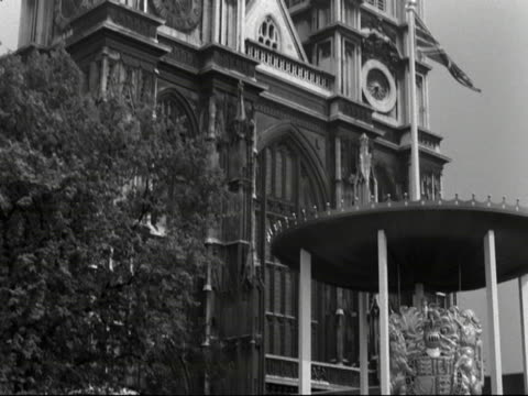 Tilt down the exterior of Westminster Abbey to crowds entering a purpose built building for the Coronation celebrations 1953