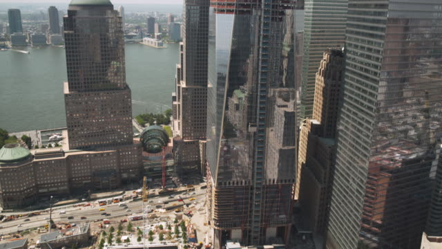 tilt down, then tilt up, the new one world trade center whilst under construction, showing the national september 11 memorial and surrounding buildings, new york city, usa, summer 2011. - standing water stock videos & royalty-free footage