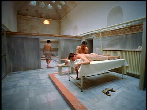 tilt down tilt up ceiling to man in towel walking + second man getting massage in Turkish bath / Istanbul