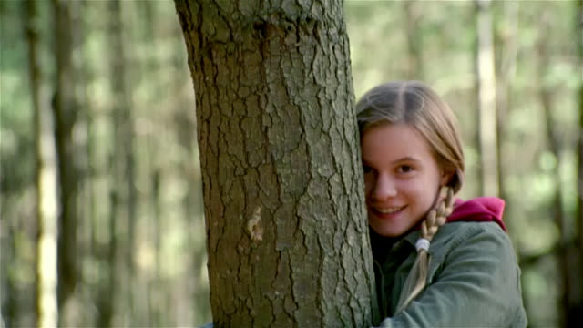 tilt down tilt up girl hugging tree in woods and smiling at camera - tree hugging stock videos & royalty-free footage