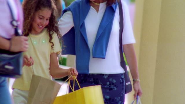 ms tilt down tilt up hispanic woman + girl carrying shopping bags walking toward camera outdoors / florida - figlia femmina video stock e b–roll