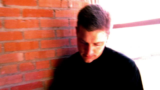 shaky high contrast ms tilt down tilt up man using pda by window in empty loft apartment / camera moving away - high contrast stock videos & royalty-free footage