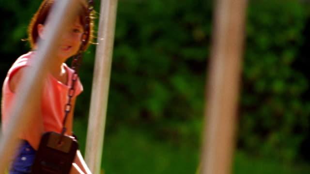 vidéos et rushes de canted ms tilt down tilt up portrait girl sitting on swing with other children swinging in foreground / florida - balançoire