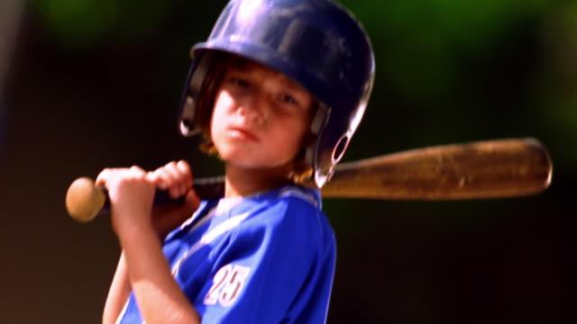 MS tilt down tilt up PORTRAIT girl wearing baseball uniform with helmet + holding baseball bat / Florida