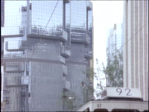 tilt down to 2 double decker trolleys on city street / hong kong - anno 1997 video stock e b–roll