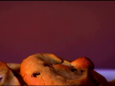 vídeos de stock, filmes e b-roll de tilt down to an extreme close-up of cookies rotating on a plate. - equipamento doméstico