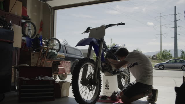 vídeos de stock e filmes b-roll de tilt down to boy repairing motorcycle in garage / lehi, utah, united states - lehi