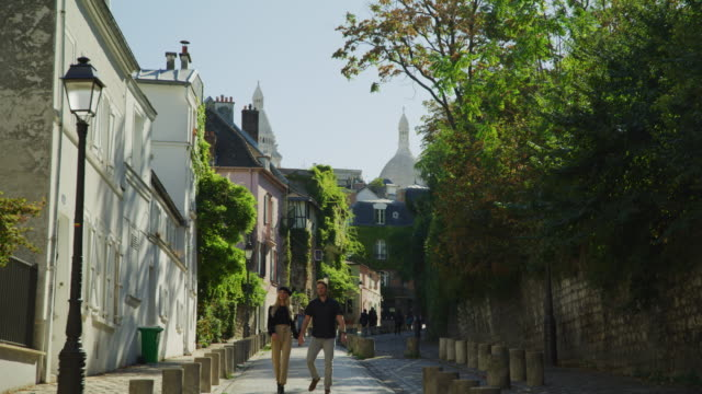 tilt down to couple sightseeing on street in montmartre neighborhood / paris, ile de france, france - france stock videos & royalty-free footage