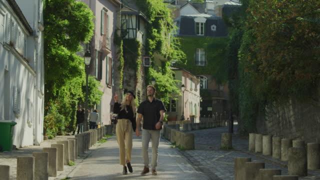 tilt down to couple sightseeing on street in montmartre neighborhood / paris, ile de france, france - basco video stock e b–roll