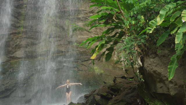 tilt down to distant happy woman standing on rocks under waterfall / carmel falls, grenada - hair toss stock videos & royalty-free footage