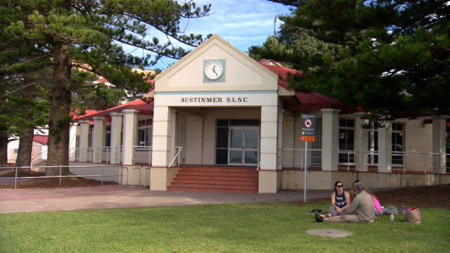 vídeos de stock e filmes b-roll de tilt down to exterior austinmer surf life saving club building flanked by norfolk island pines - family picnics on lawn / close up of clock and sign... - maça