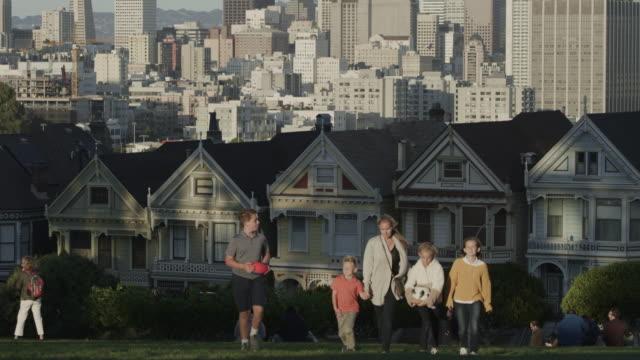 vidéos et rushes de tilt down to family walking uphill in urban park carrying football and soccer ball / san francisco, california, united states - famille avec quatre enfants