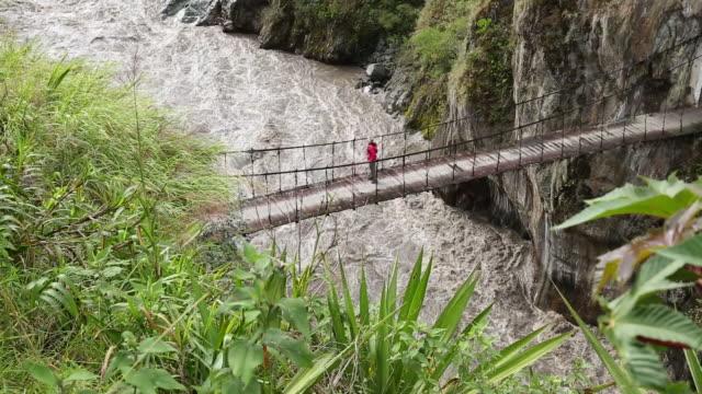 tilt down to female hiker crossing suspension bridge - einzelne frau über 40 stock-videos und b-roll-filmmaterial