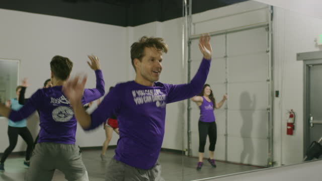 vídeos y material grabado en eventos de stock de tilt down to fitness instructor dancing in exercise class near mirror / american fork, utah, united states - encuadre de tres cuartos