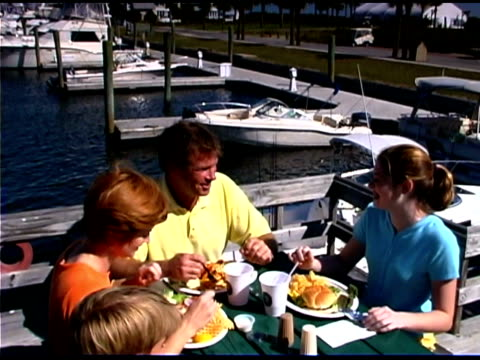 tilt down to high angle view shot of family eating near marina - see other clips from this shoot 1335 stock videos and b-roll footage