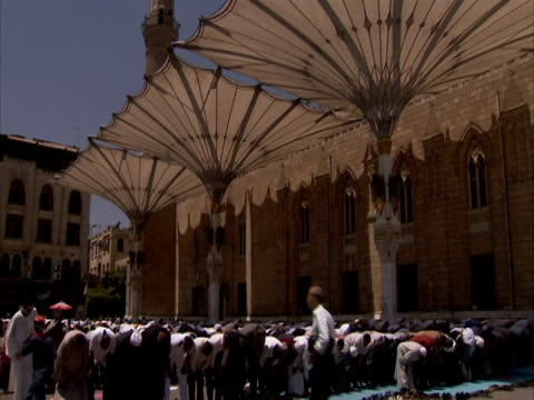 stockvideo's en b-roll-footage met tilt down to many people, bowing in prayer outside, islamic area of cairo, egypt (sound available) - bukken