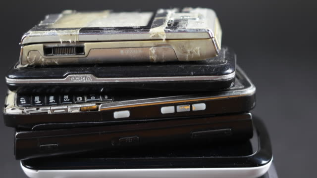 Tilt down to multiple cell phones on top of each other, E-waste multiple discarded electronic appliance sold mobile smart cell phones