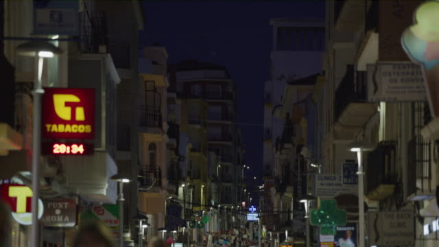 vídeos de stock e filmes b-roll de tilt down to people walking in crowded city street at night / ronda, malaga, spain - inclinação para baixo