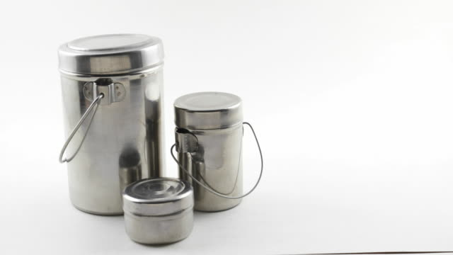 tilt down to set of indian kitchen utensils in stainless steel in white isolated background - ステンレス点の映像素材/bロール