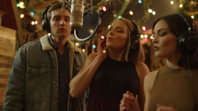 tilt down to singers wearing headphones recording vocals with microphone / provo, utah, united states - no doubt band stock videos & royalty-free footage