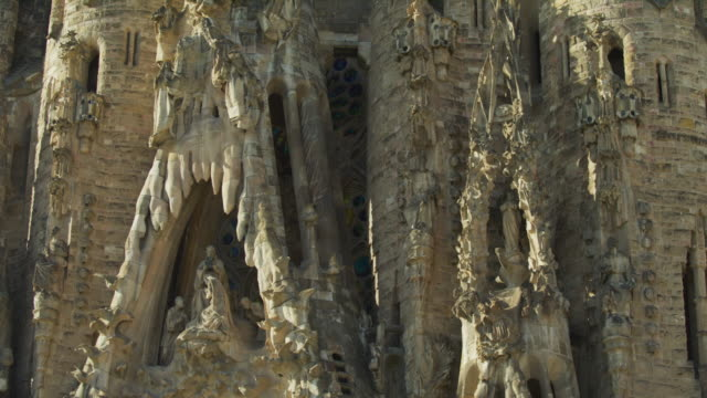 tilt down to statues and ornate facade of la sagrada familia / barcelona, barcelona, spain - sagrada familia stock-videos und b-roll-filmmaterial