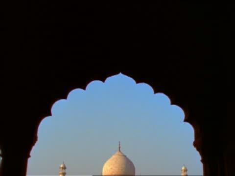 vídeos de stock e filmes b-roll de tilt down to taj mahal framed by silhouetted archway / india - taj mahal