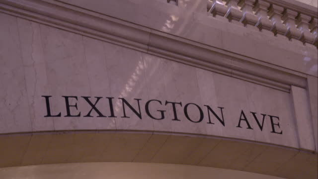 tilt down to the lexington ave sign in the main concourse of grand central terminal in manhattan - western script stock videos & royalty-free footage