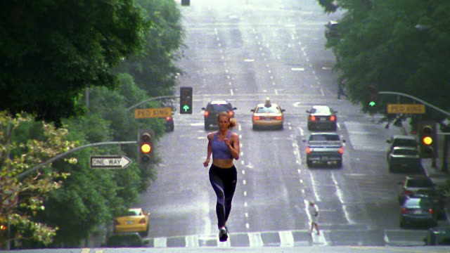 tilt down to wide shot woman jogging on hilly city street / los angeles - sportbehå bildbanksvideor och videomaterial från bakom kulisserna
