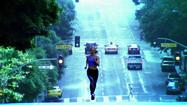 stockvideo's en b-roll-footage met tilt down to wide shot woman jogging on hilly city street / los angeles - elasthaan
