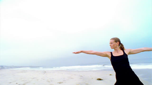 "stockvideo's en b-roll-footage met tilt down to wide shot woman performing ""warrior"" yoga pose on beach / los angeles - noordelijke grote oceaan"