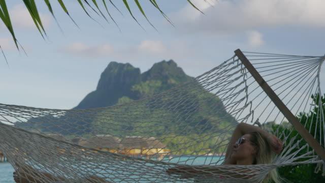 tilt down to woman relaxing in hammock on ocean beach in tahiti / bora bora, french polynesia - bora bora stock videos and b-roll footage
