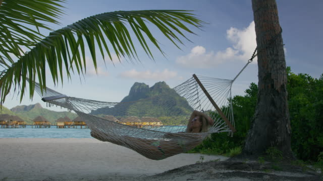 vídeos de stock, filmes e b-roll de tilt down to woman relaxing in hammock on ocean beach in tahiti / bora bora, french polynesia - polinésia francesa