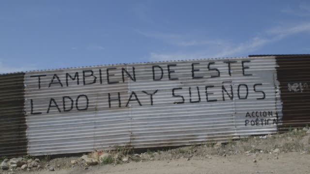 stockvideo's en b-roll-footage met tilt down to words on mexican side of border wall translating to there are dreams on this side, too - internationale grensbarrière