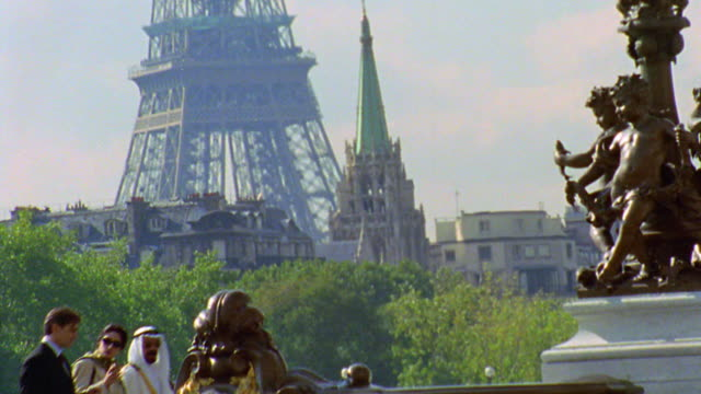 tilt down traffic + 3 businesspeople (1 arab) walking on pont alexandre iii with eiffel tower in background / paris - pont alexandre iii stock videos & royalty-free footage