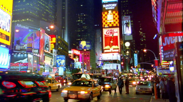 stockvideo's en b-roll-footage met tilt down traffic and people on street in times square at night / midtown manhattan, new york city - gele taxi