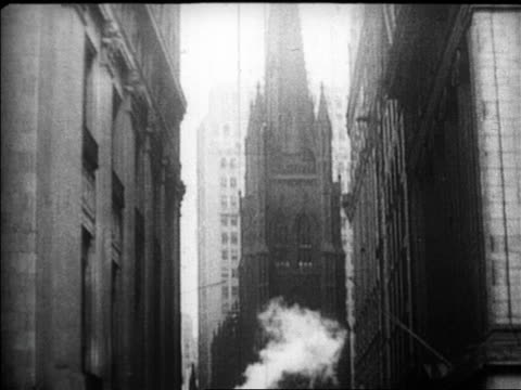 vídeos de stock, filmes e b-roll de tilt down trinity church to crowds on wall street / newsreel - 1920 1929