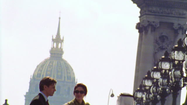 canted tilt down two businessmen (1 arab) + woman talking on pont alexandre iii / les invalides in background - dischdascha stock-videos und b-roll-filmmaterial