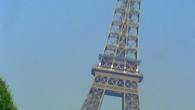 canted tilt down two businessmen (1 arab) + woman walking toward camera with eiffel tower in background / paris - female with group of males stock videos & royalty-free footage