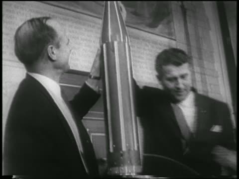 vídeos de stock e filmes b-roll de b/w 1958 tilt down two men holding model of rocket / werner von braun william pickering - 1958