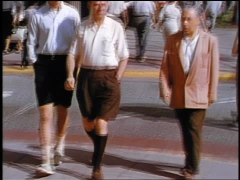 1957 tilt down two men in shorts walking outdoors / feature