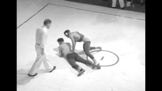 Tilt down two wrestlers standing on mat one has jacket on that reads CASE 14 the other has sweatshirt over shoulders ref holds up arm of winner...
