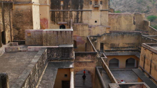 a tilt down view of the narrow lanes and pathways inside the amer fort in jaipur, rajasthan - calle principal calle video stock e b–roll