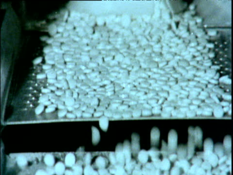 Tilt down white pills bouncing up and down while travelling along conveyor belt in pharmaceutical factory