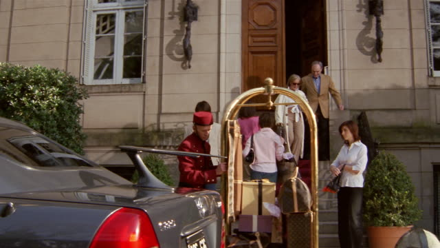 tilt down wide shot wealthy man and woman leaving hotel + getting into limousine / bellman loading luggage - einkaufstasche stock-videos und b-roll-filmmaterial