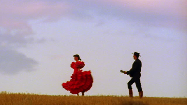 tilt down woman in red flamenco dress dancing next to man in hat playing guitar on plain / spain - flamenco dancing stock videos and b-roll footage