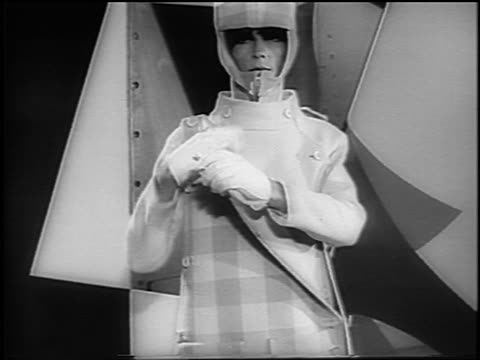 b/w 1965 tilt down woman modeling coat + hood removing vest + posing indoors / nyc / newsreel - anno 1965 video stock e b–roll