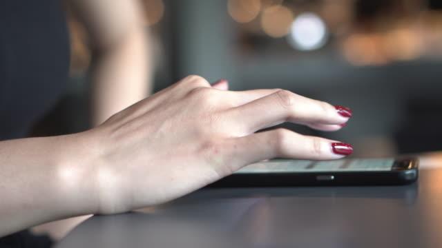 vídeos y material grabado en eventos de stock de incline hacia abajo mujer jugar móvil en café con fondo naranja - esmalte de uñas rojo